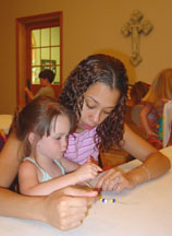 Caleigh and Daphne work on a bracelet