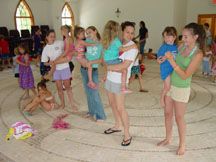 Helpers holding kids while singing