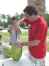 Father Frank cuts the watermelon